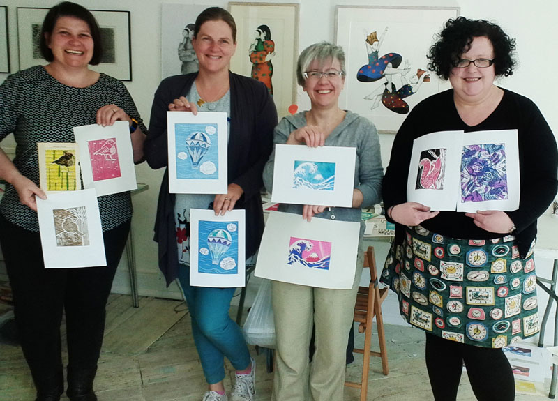 Happy students showing their linocut prints at the end of the workshop