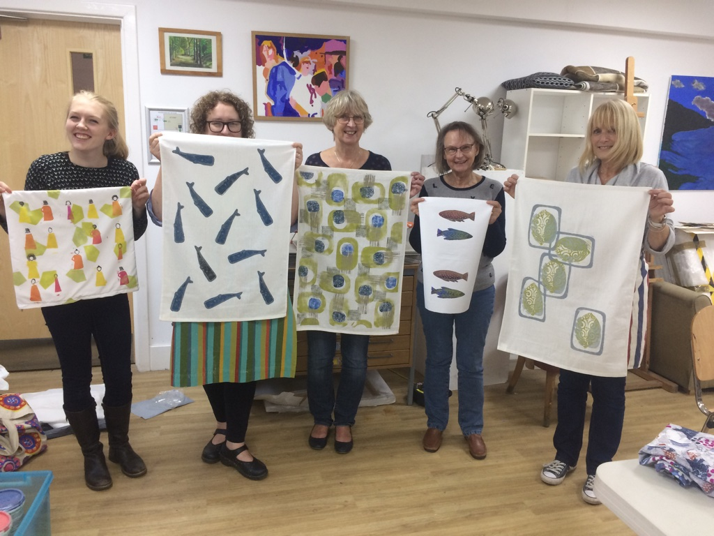 Happy students holding up their block printed textiles.